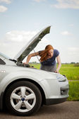 A woman having troubles with her car