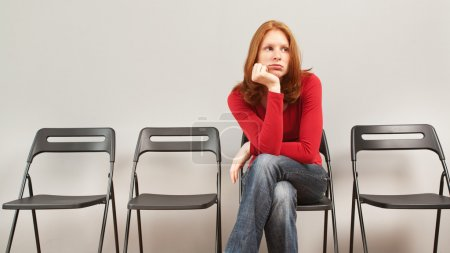 Photo for A young woman sitting in an empty waiting room and looking bored. - Royalty Free Image