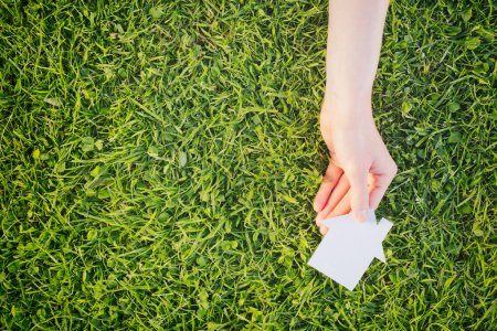 Photo for Real estate business concept - hand of a businesswoman or a buyer holding a white cutout house over green grass. - Royalty Free Image
