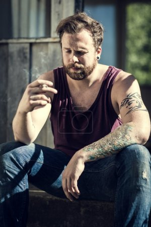 Punker sitting on staircase and smokes
