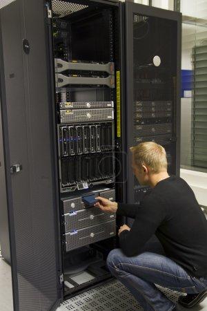 Photo pour Un travail ingénieur / technicien insérer une bande de sauvegarde dans un robot de sauvegarde dans la grille. tourné dans un data center. - image libre de droit
