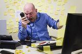 Rozhněvaný muž křičí v telefonu