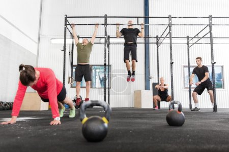 Photo for A group training push ups, hang ups and squat at a crossfit center. - Royalty Free Image