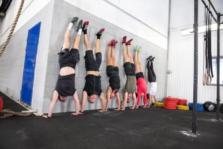 Photo for Group does handstand in a workout session at fitness center. - Royalty Free Image