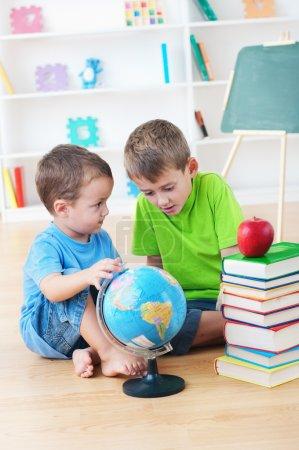 Photo pour Deux petits garçons étudient la géographie ensemble - image libre de droit