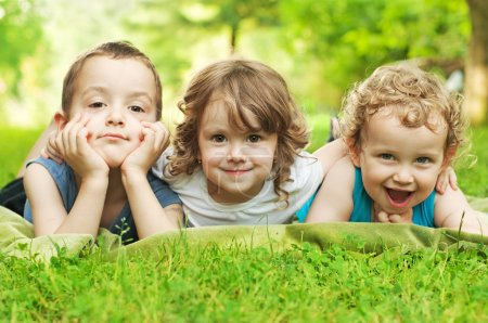 Photo for Three happy children resting on the green grass - Royalty Free Image
