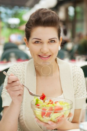 Photo for Happy Young Woman Eating Outdoors - Royalty Free Image
