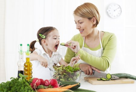 Photo for Mother feeding child, while chopping vegetable - Royalty Free Image