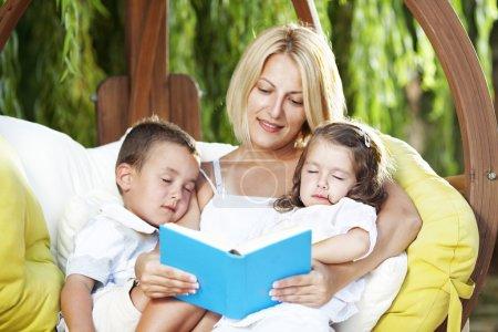 Photo pour Livre de lecture de mère à ses enfants alors qu'ils la sieste en plein air sur une balançoire - image libre de droit