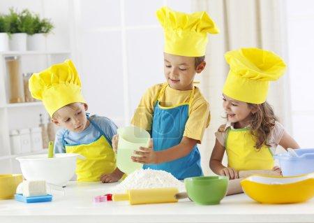 Three children baking