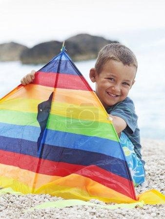 Photo pour Enfant assis sur la plage souriant et jouant avec le cerf-volant - image libre de droit
