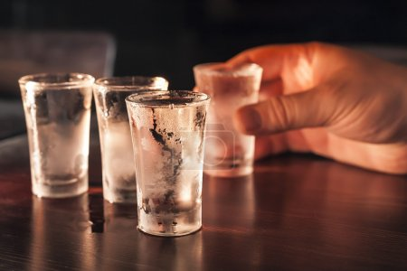 Photo for Four full shot glasses of vodka on a wooden table, one in hand. - Royalty Free Image