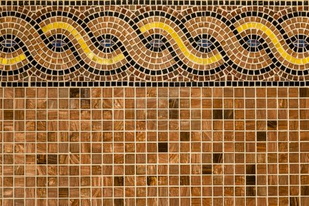 Mosaic in ancient style stacked with tiny brown, yellow, blue tiles.