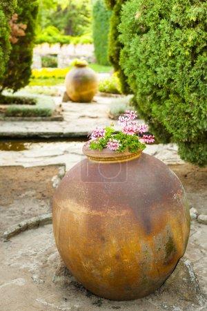 Clay amphora standing in garden.