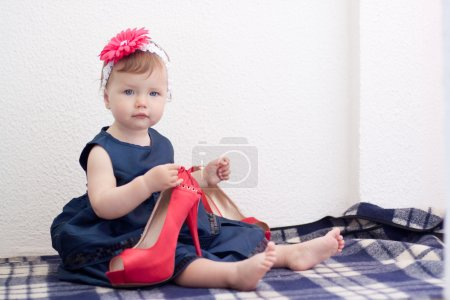 Photo pour Enfant tient adulte chaussures à talons hauts - image libre de droit