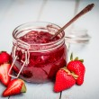 Strawberry jam in a jar on wooden background...