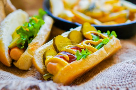Hot Dogs with french fries in the skillet on wooden background