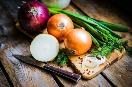 Photo for Colorful onions and garlic on rustic wooden background - Royalty Free Image