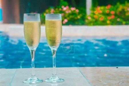 Photo pour Champagne près de la piscine - image libre de droit