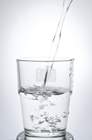 Filling a glass with water showing a drink concept