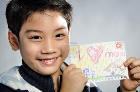 "Little asian boy holding picture wiith word ""I love mom"" ."