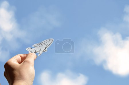 Hand holding paper plane on a sky background