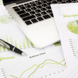 Laptop and pen with green business charts, graphs,...