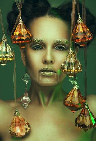 Photo pour Belle fille avec visage d'art et pendentifs en cristal . - image libre de droit