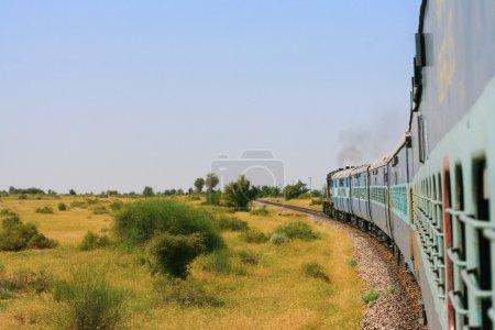 Indian train driving through across the plain.