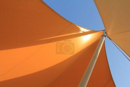 Overhead awnings on a pole against blue sky