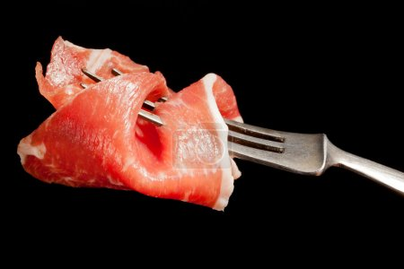 Photo for Delicious culinary prosciutto ham on silver fork isolated on black background. Culinary appetizer eating. - Royalty Free Image