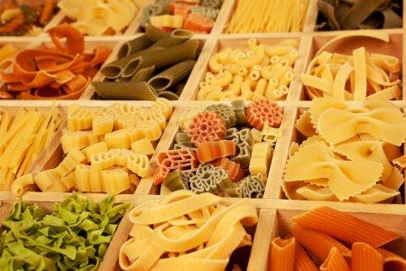 Photo pour Diverses pâtes colorfull trie en détail dans une boîte en bois. - image libre de droit