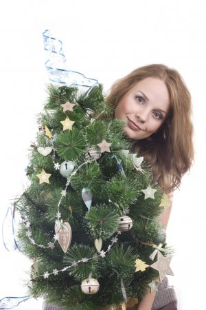 Beautiful smiling blond girl with Christmas tree dressed up in her arms on a white background