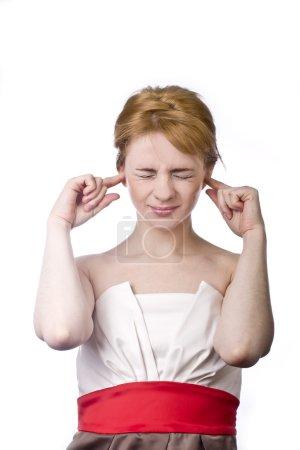 Photo pour Jeune blonde en colère couvre ses oreilles avec ses mains - image libre de droit