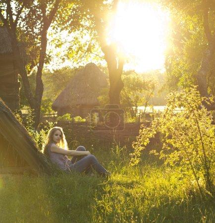 Photo pour Belle blonde frisée aime le soleil dans la campagne. rayons du soleil dans les cheveux. style campagnard. maison de campagne. météo parfaite. - image libre de droit