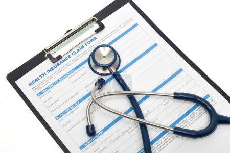 Photo pour Formulaire de demande d'assurance médicale et maladie avec stéthoscope sur presse-papiers isolé - image libre de droit