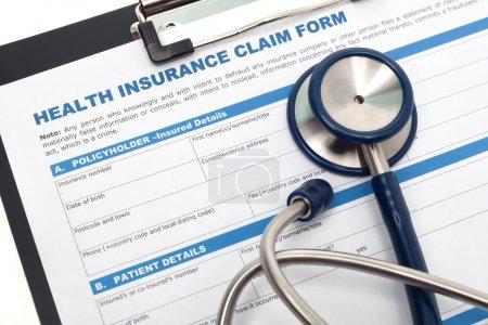 Photo pour Formulaire de demande d'assurance médicale et maladie avec stéthoscope sur presse-papiers - image libre de droit