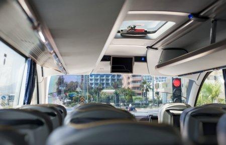 Photo pour Photographie d'intérieur d'autocar vide de la derrière des sièges. autobus attend au feu rouge et il va obtenir des passagers de la gare. - image libre de droit