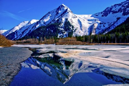 Photo for Partially Frozen Lake with Mountain Range Reflected in the Great Alaskan Wilderness. A Beautiful Landscape of Blue Sky, Trees, Rock, Snow, Water and Ice. Near Seward highway near Anchorage, Alaska. - Royalty Free Image