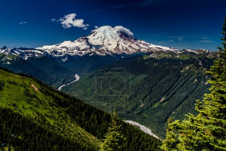Beautiful Snow Capped Mount Rainier with a Deep River Valley, Clear Blue Skies, Green Pine Trees, and Crisp Mountain Air.