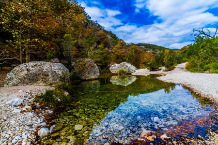 A Picturesque Scene Bursting with Beautiful Fall Foliage and Large Granite Boulders on a Tranquil Babbling Brook at Lost Maples State Park in Texas.