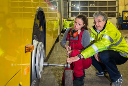Photo for Yong woman, trainee with the master, change wheel of a Buses in the work hall - Royalty Free Image