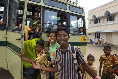 Indian children get on a school bus after visiting a church service in Vizhinjam, Kerala, India.