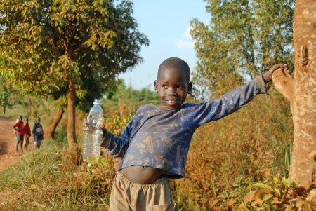 Photo pour Petit mendiant sur la route de Murchison Falls le 9 décembre 2007 près de Masindi, Ouganda. Mendier pour les touristes est courant pour les enfants dans les zones rurales de l'Ouganda . - image libre de droit
