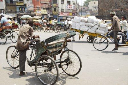 Indian rickshaw man waits his passengers on a street in New Delhi, India.
