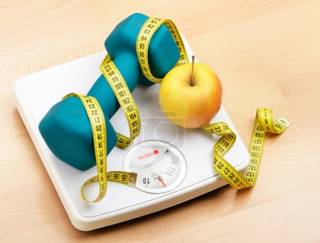 Photo for Fresh apple and dumbbells tied with a measuring tape on a weighting scale - Royalty Free Image