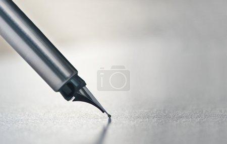 Photo pour Gros plan d'un stylo plume écrit sur un morceau de papier - image libre de droit