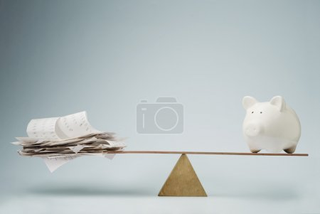 Photo for Piggy bank balancing on seesaw over a stack of bills - Royalty Free Image