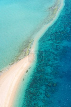 Photo for Aerial view looking down at sand beach surrounded by fringing coral reef and clear blue sea. Photo taken at Langford Island, Great Barrier Reef Marine Park, Whitsunday, Australia. - Royalty Free Image