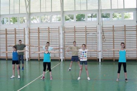 Photo pour Les jeunes femmes et les hommes dans la salle de gym debout pour la calisthénique - image libre de droit